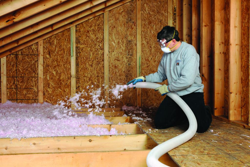 worker installing blown in attic insulation