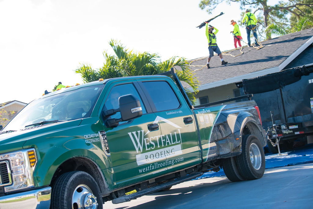 Westfall Roofing truck in front of a home with roofing team working on the roof