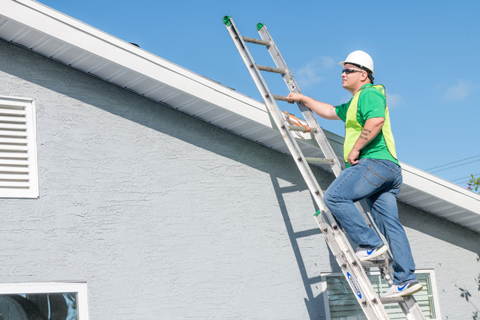 Roofer in safety gear on a ladder at the edge of a roof