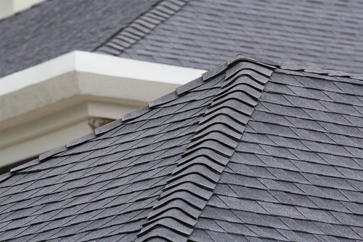 edge of Roof shingles on top of the house, dark asphalt tiles on the roof background