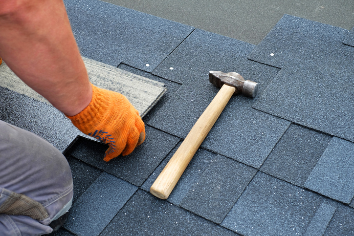 Contractor hands installing bitumen roof shingles using hammer in nails.